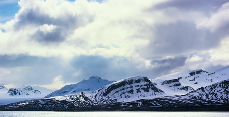 artic circle: Dramatic clouds over mountains covered with snow in the cold arctic environment in Svalbard.