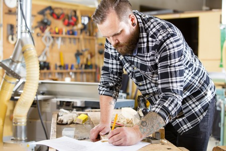 causal clothing: Adult craftsman looks at drawing in a work shop for wood work and construction. Carpenter designs and prepares new work.