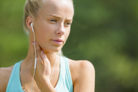 resting heart rate: Young athletic woman checking her heart rate after workout outdoor. Stock Photo