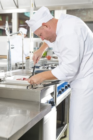 gourmet kitchen: Close-up of a dedicated chef prepares beef steak dish in a pan at a professional kitchen. Gourmet restaurant or hotel.