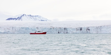 calving: Expedition or tourist boat in front of the large and massive Borebreen glacier. Arctic environment in Oscar II Land at Spitsbergen, Svalbard.