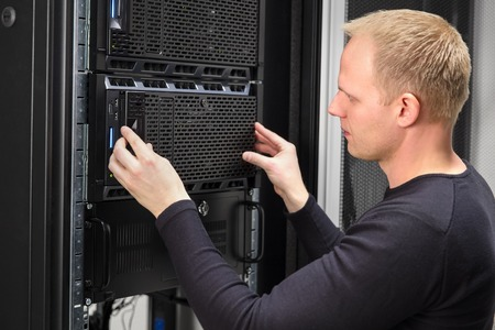 server side: It engineer or technician work with servers in data rack. Shot in large datacenter.