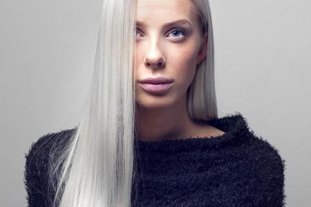 Hermosa mujer de moda joven con el pelo rubio largo y negro de la chaqueta de diseño peludo. Fotografía de estudio. apaisada gris.