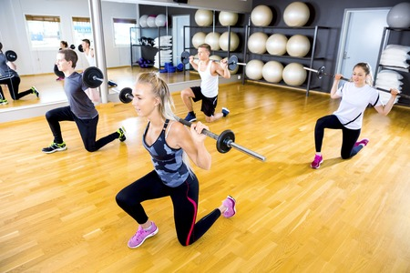 fitness motivation: Smiling and dedicated workout group doing split squats with weights at the shoulders in fitness gym. Teamwork and motivation.