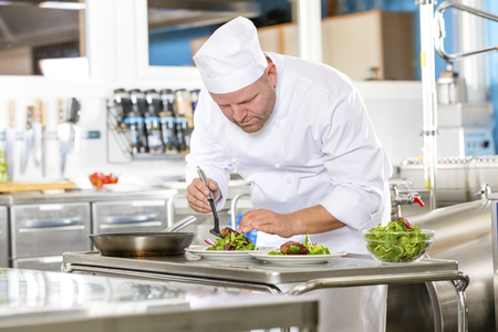 chef kitchen: Professional chef prepares beef meat dish in a large professional kitchen at gourmet restaurant or hotel. Stock Photo