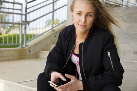 Lächelnde schöne Frau in einer Treppe in der Stadt sitzt, eine Jacke und Workout-Outfit. Hört Musik auf ihrem Smartphone. Standard-Bild - 63384741