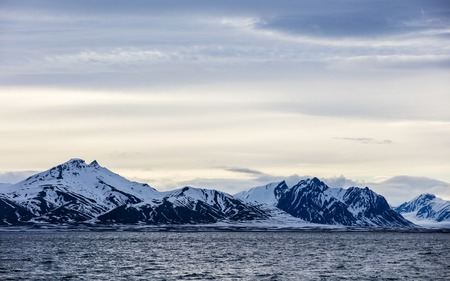 artic circle: Clouds over mountains covered with snow in the cold arctic environment in Svalbard.