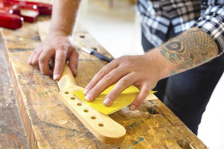 planos electricos: El uso de papel de lija artesano en un cuello de la guitarra en un taller de madera. hombre de trabajo duro con el tatuaje se trabaja con instrumentos musicales.