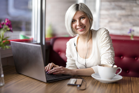doing business: Happy blonde woman with laptop computer drinking coffee and doing business or study in a cafe.