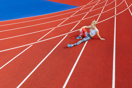 sports track: Fit athlete woman sits and rests on a running track at sports arena. Female sprinter after running.