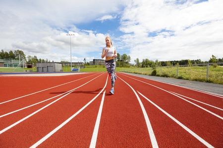 Female corridore atleta o velocista sulla pista corrente. Allenamento all'aperto.