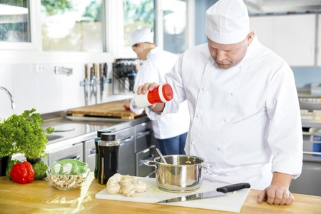 industrial kitchen: Professional chef add salt in food at a industrial kitchen in hotel or restaurant. Assistant or chef working in the background.