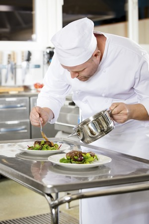 adds: Focused chef adds gravy to a meat dish in a professional kitchen at gourmet restaurant or hotel.