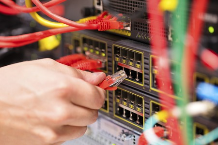 IT technician or engineer connects a gigabit network cable into switch in datacenter Standard-Bild