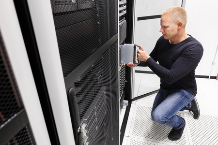 server side: It engineer or consultant working with installation of a blade server in data rack. Shot in enterprise datacenter.
