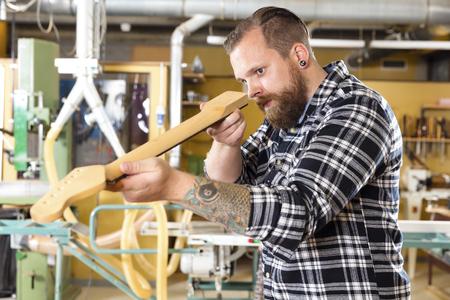 planos electricos: Craftsman inspecciona un cuello de la guitarra en un taller de madera. hombre de trabajo duro con el tatuaje y la barba se trabaja con instrumentos musicales.