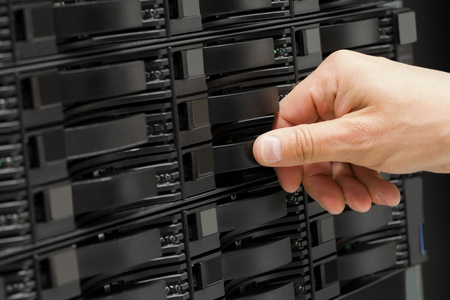 disks: IT technician or engineer working with hard drives in a storage array network. Data backup in a large datacenter. Stock Photo