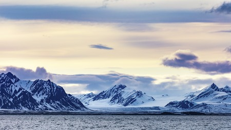 artic circle: Clouds over mountains covered with snowand glacier in the cold arctic environment in Svalbard. Stock Photo