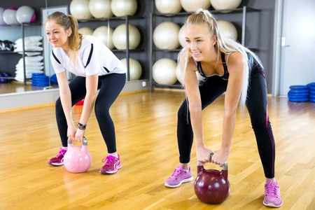 fits in: Group workout at a fitness center. Kettlebell weight workout at the gym.