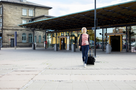 wheeled: Full length of young woman with wheeled luggage walking outside train station