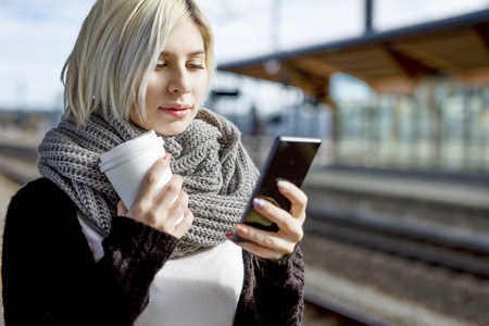 messaging: Young woman with coffee cup using mobile phone while waiting for train at station