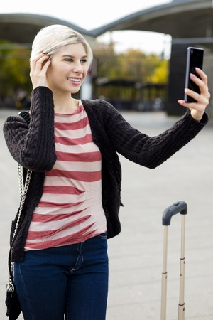 Beautiful young woman taking selfie with mobile phone outside railroad station