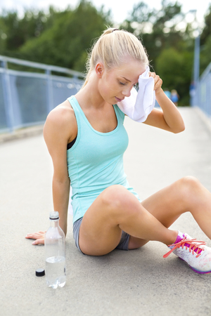 Young athletic female runner rests after running or jogging training outdoor. Drinks water and dries her face with a towel on a bridge.