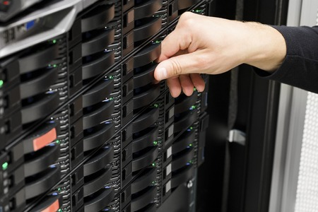 Closeup of male IT technicians hand replacing hard drive in SAN at data center