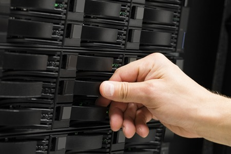 replacing: Closeup of male engineers hand replacing hard drive in SAN storage at datacenter Stock Photo