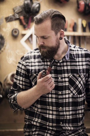 Environmental portrait of a young adult craftsman sitting and smoking a pipe tobacco in a workshop for wood work and construction. Stock Photo