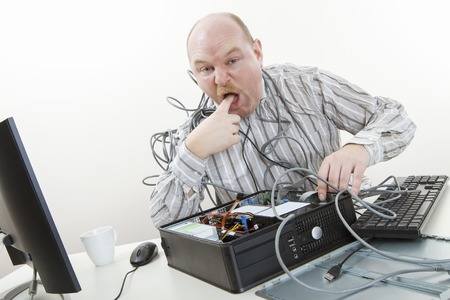 licking finger: Portrait of irritated businessman licking finger while repairing computer in office