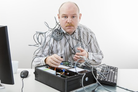 Portrait of mature technician repairing computer at desk in office