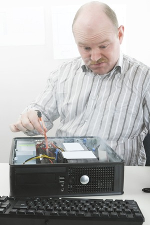 chassis: Disgust mature businessman looking at smoke coming out from computer chassis while repairing it in office