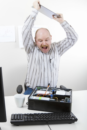 banging: Furious mature businessman banging file on computer chassis at table in office
