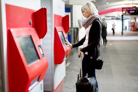 Zijaanzicht van de jonge vrouw met bagage kopen treinkaartje met behulp automaat op het station