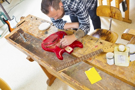 Top view of a adult crafts man who works with a music instrument in a workshop for wood work and painting. Stock Photo