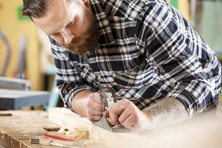 planos electricos: Artesano trabajando duro trabajo con cepillo en un taller de carpintería. Hombre hermoso con el tatuaje y la barba.