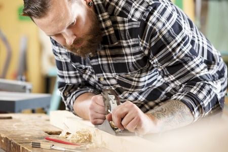 craftmanship: Hard working craftsman working with planer in a workshop for woodwork. Handsome man with tattoo and beard. Stock Photo