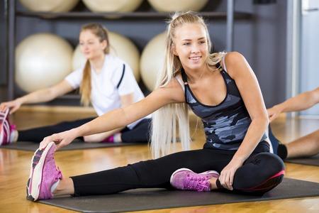 Sorridente giovane donna in cerca di distanza mentre streching e tenendo premuto il dito del piede in palestra. squadra allenamento facendo excerises di stretching per la flessibilità e l'equilibrio in palestra.