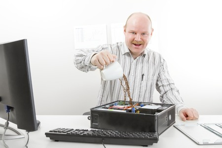 chassis: Portrait of crazy mature businessman pouring coffee in computer chassis on table in office