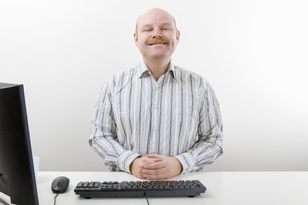 Portrait of confident businessman smiling at computer desk in office