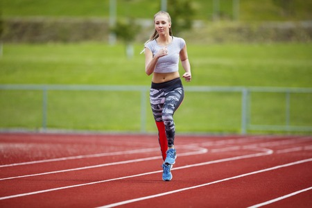 sports track: Full length of young woman in sportswear running on sports track Stock Photo