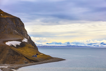 artic circle: Houses in a mountain side in the arctic landscape. Clouds over mountains covered with snow in the cold arctic environment at Svalbard.