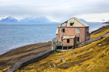 artic circle: Abandoned house in Barentsburg settlement. Clouds over mountains covered with snow in the cold arctic environment at Svalbard.