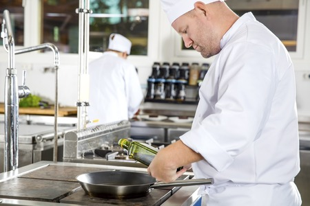 gourmet kitchen: Two chefs working in gourmet restaurant or hotel. Chef pours olive oil in a pan in a professional kitchen.