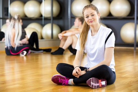 full length mirror: Full length portrait of confident young woman sitting cross legged in fitness center Stock Photo