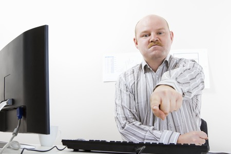 bossy: Bossy mature businessman pointing at computer desk in office. Angry and furious leader.
