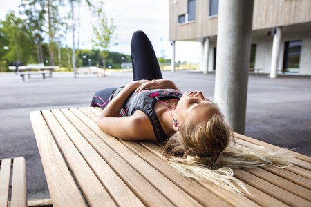 agotado: Sporty young woman listening music while lying on wooden bench. Rests after workout.