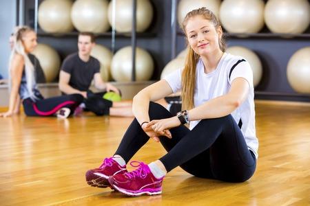 atletismo: la mujer del ajuste en traje de entrenamiento sonriendo en el gimnasio de fitness