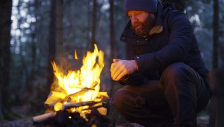 男は森の中のキャンプの火で彼自身を温め